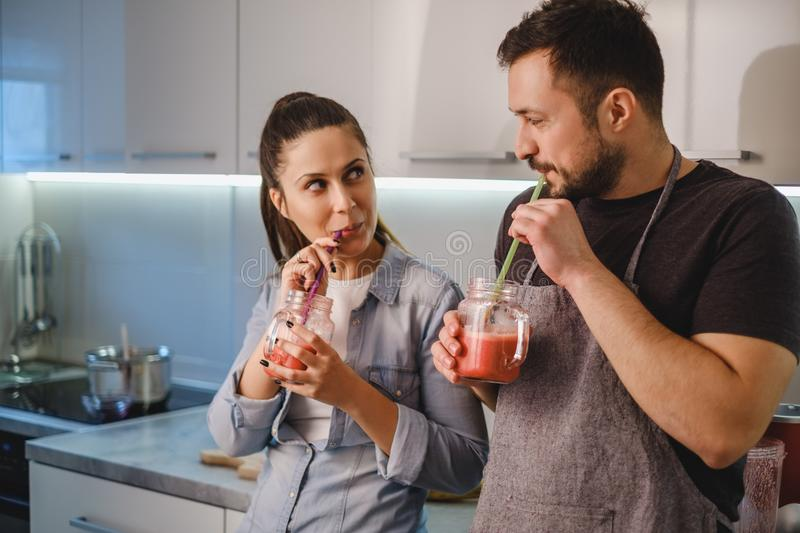 Couple flirting in the kitchen while drinking smoothie. With a straw royalty free stock photos