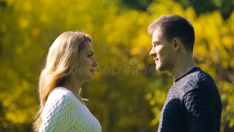 Couple flirting and looking at each other in autumn forest, together forever. Stock photo stock photography