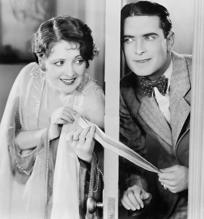 Couple flirting through a slightly open door royalty free stock photos