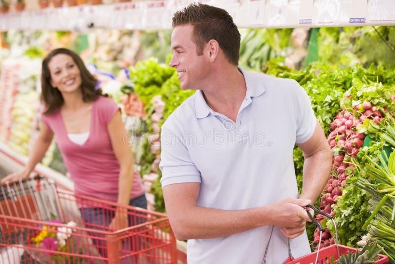 Couple flirting in supermarket. Aisle royalty free stock image