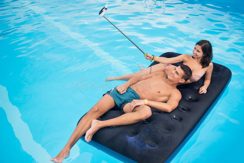 Couple floating on mattress in pool and taking selfie photo on the phone with selfie stick on their summer vacation royalty free stock photography