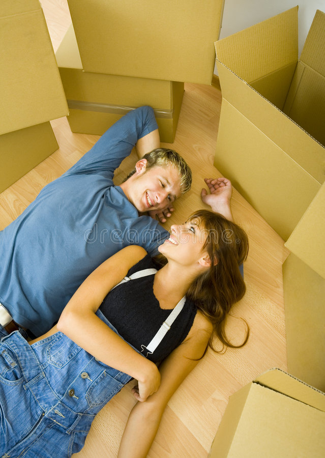 Couple on the floor. Young, happy couple lying on the floor in flat and resting.They're looking at each other. Front view stock photos