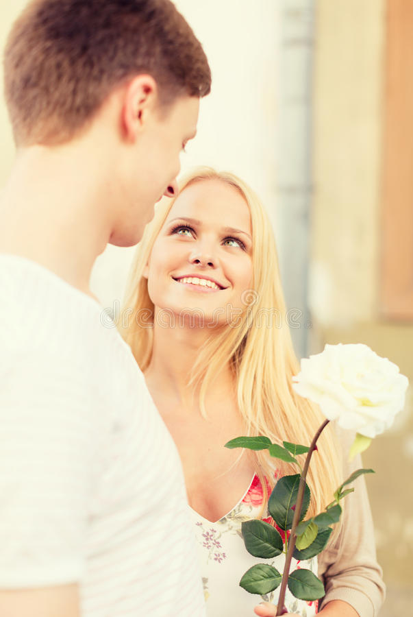 Couple with flowers in the city. Summer holidays, love, relationship and dating concept - couple with bouquet of flowers in the city stock photography