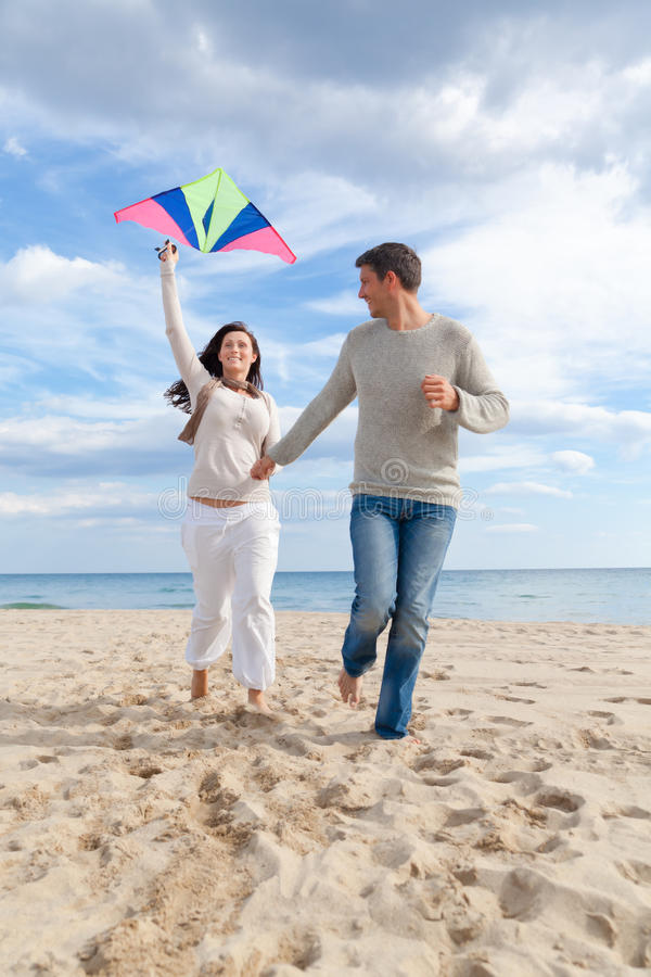 Couple fly kite. Happy outdoor autumn winter spring couple embracing and running on beach a kite fly