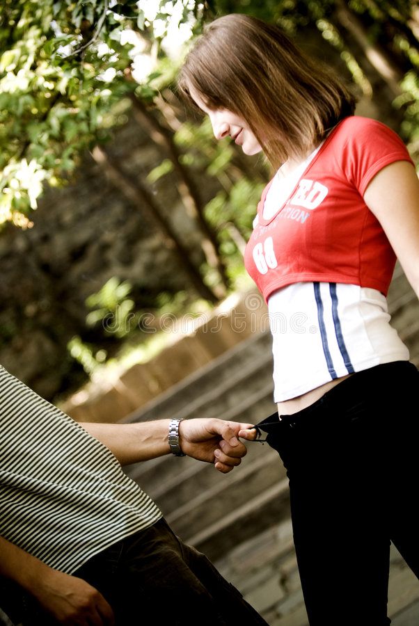 Couple fooling around in park. Young couple fooling around in a park, man wearing striped shirt is tugging on the belt holder of the woman. She is looking at him stock photo
