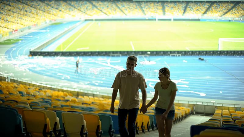 Couple of football fans leaving stadium after game, dating at sport event. Stock photo royalty free stock images