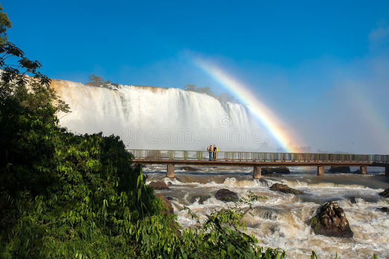 Couple in Footbridge with rainbow in Iguazu falls. National park royalty free stock photography