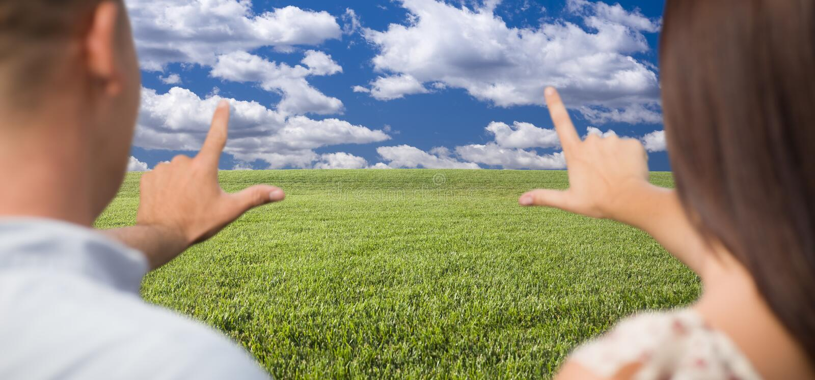 Couple Framing Hands Around Space in Grass Field royalty free stock image