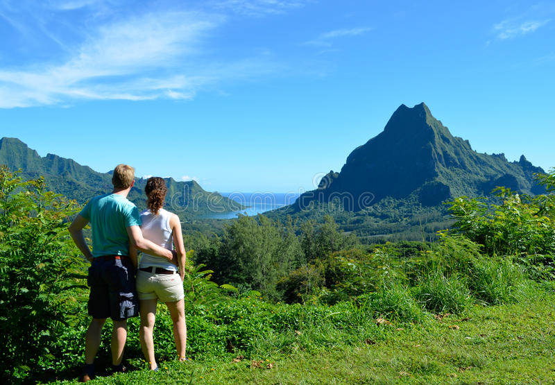 Couple in French Polynesia. Young honeymoon couple with an overview over Rotui mountain and Opunohu Bay on the tropical pacific island of Moorea, near Tahiti in royalty free stock images