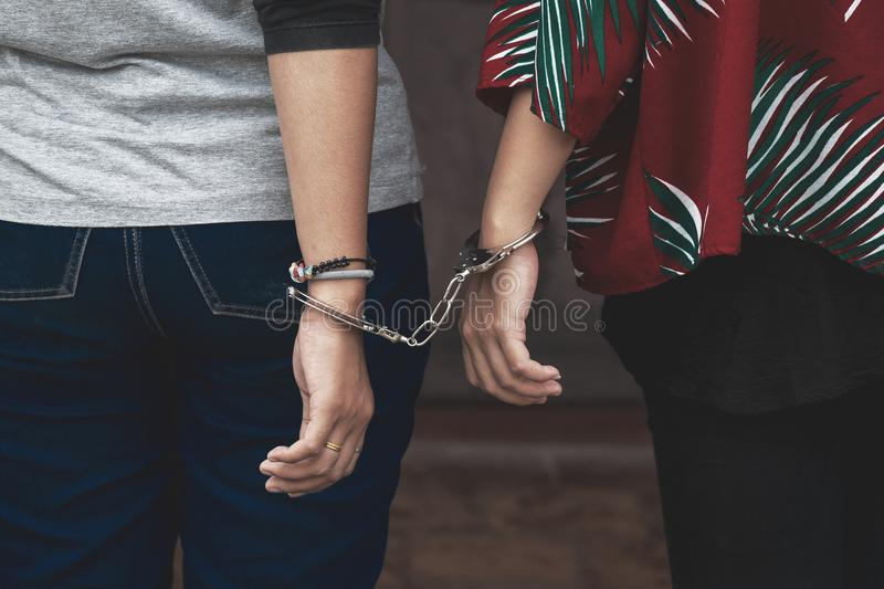 Couple Friend of Women under Arrest, Criminal Scence of Women ge. T Caught with Handcuffed by the Policeman. Concept Picture of Prisoner or Slave royalty free stock photos