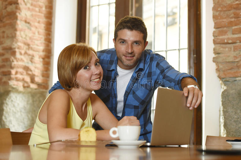 Couple or friends at coffee shop working with laptop computer in the morning happy. Young attractive couple or friends at coffee shop working with laptop royalty free stock photos