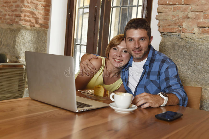 Couple or friends at coffee shop working with laptop computer in the morning happy. Young attractive couple or friends at coffee shop working with laptop royalty free stock photography