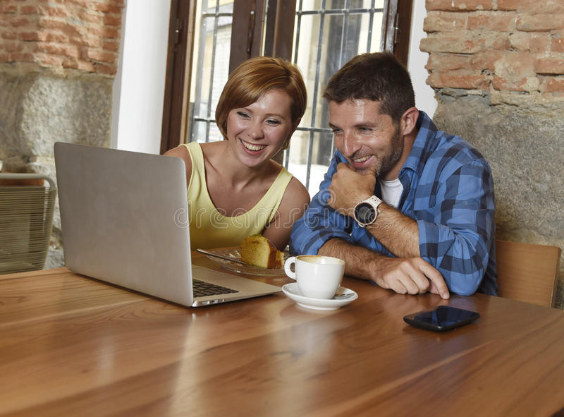 Couple or friends at coffee shop working with laptop computer in the morning happy. Young attractive couple or friends at coffee shop working with laptop royalty free stock image
