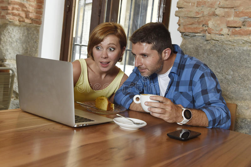 Couple or friends at coffee shop working with laptop computer in the morning happy. Young attractive couple or friends at coffee shop working with laptop stock image