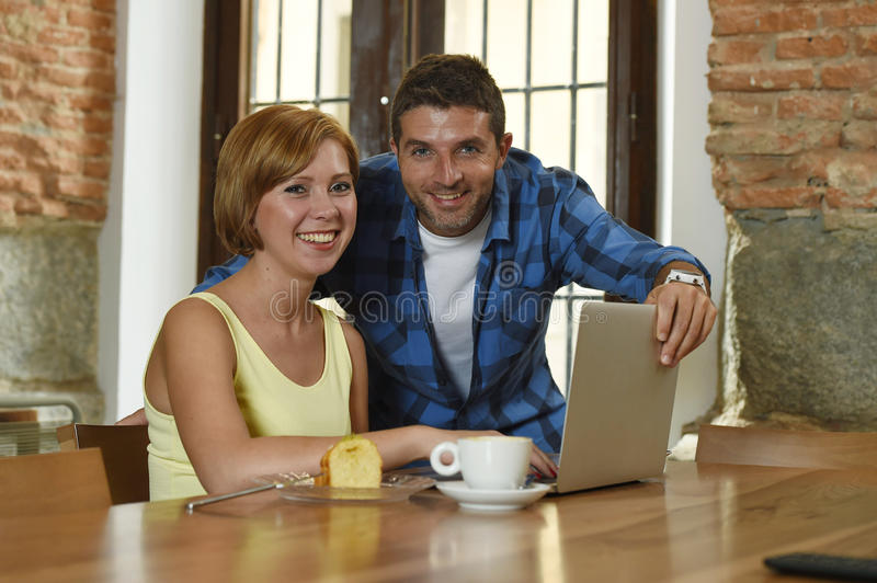 Couple or friends at coffee shop working with laptop computer in the morning happy. Young attractive couple or friends at coffee shop working with laptop stock photography