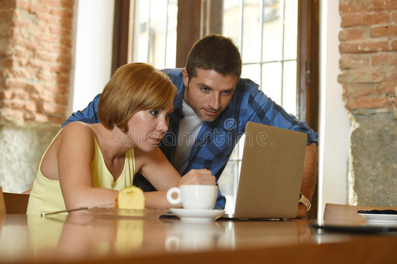 Couple or friends at coffee shop working with laptop computer in the morning happy. Young attractive couple or friends at coffee shop working with laptop royalty free stock images