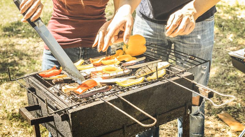 Couple of friends cooking vegetables on barbecue - Aubergines and peppers cooked on grill at bbq garden party - Pic nic concept stock image