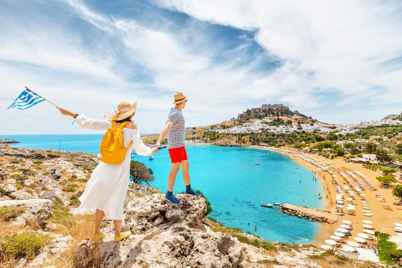 Couple of friends in love with the Greek flag admire the grandiose view of the sea Bay and the beach near the ancient city of. A couple of friends in love with stock image