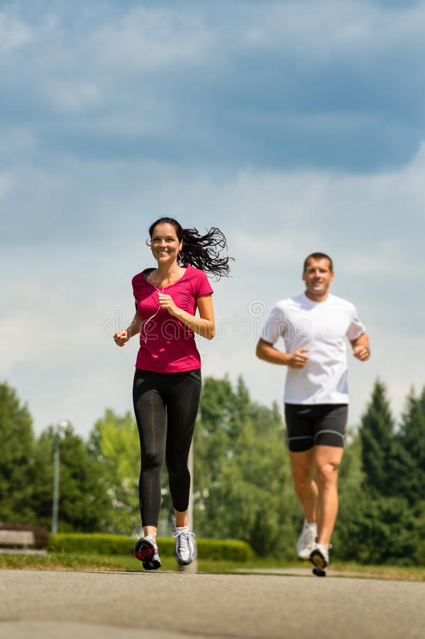 Couple friends running a race in park stock photography