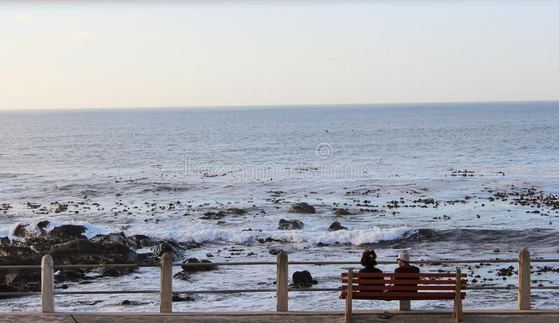 Couple or friends sitting on a bench by the beach stock image