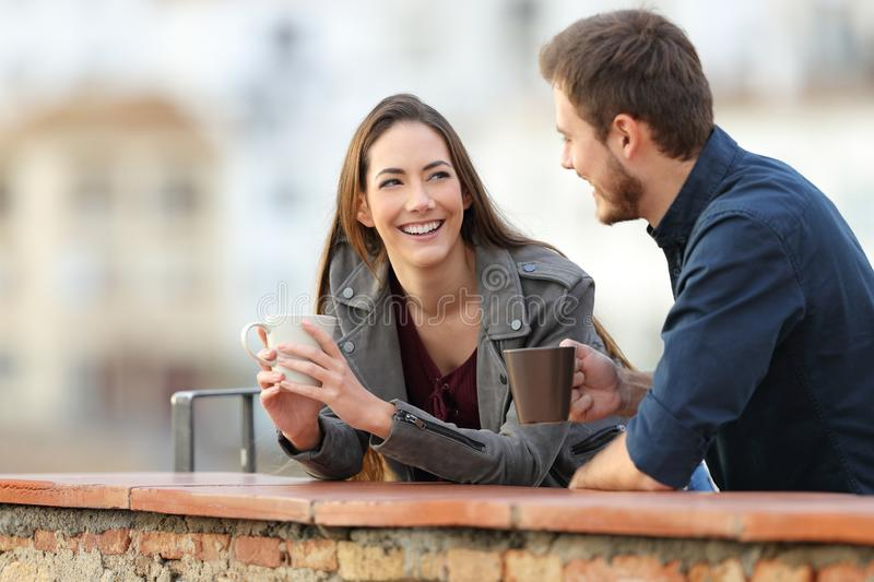 Couple or friends talking in a terrace drinking coffee. Happy couple or friends talking and drinking coffee in a rural apartment terrace on vacation royalty free stock image