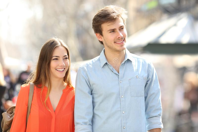 Couple or friends walking in the street looking at side royalty free stock image