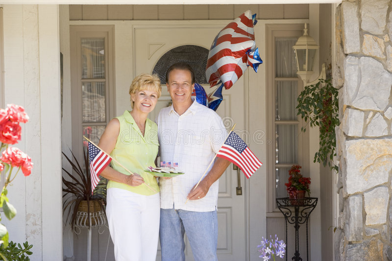 Couple At Front Door On Fourth Of July With Flags Royalty Free Stock Images