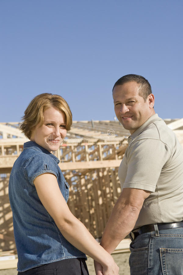 Couple In Front Of House Under Construction. Portrait of happy mature couple in front of house under construction stock photo