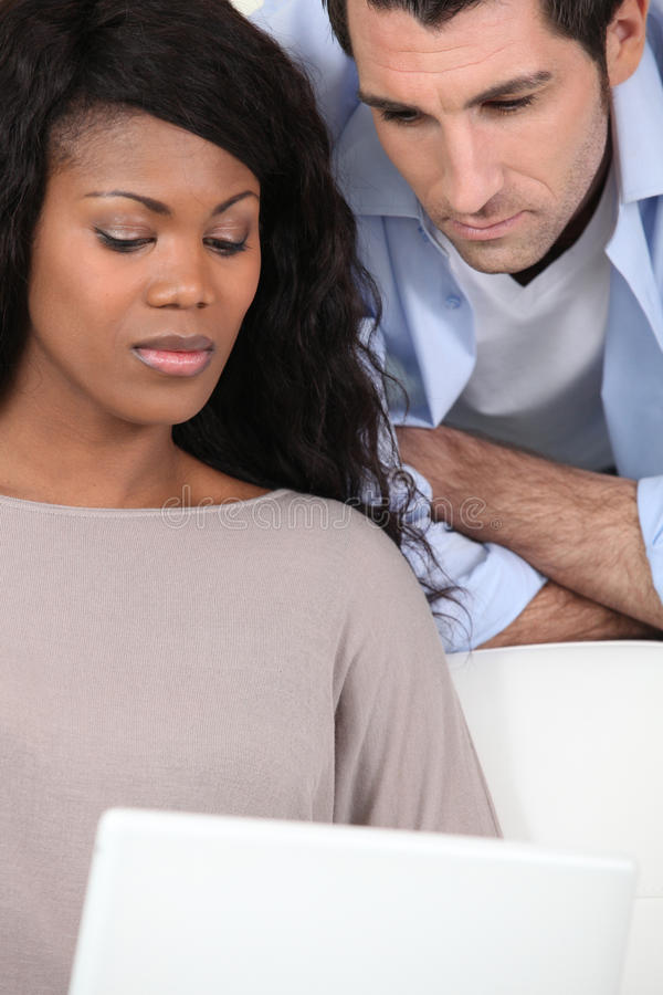 Couple in front of laptop. Man and women in front of laptop stock photography