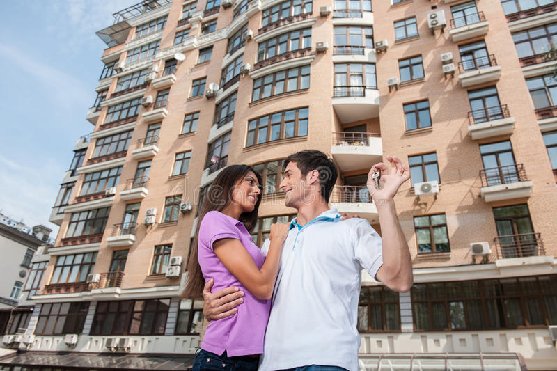 Couple in front of new home holding door keys and looking at each other. royalty free stock photos