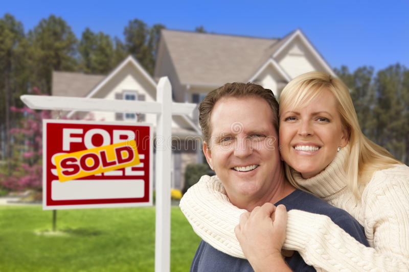Couple in Front of Sold Real Estate Sign and House. Happy Couple Hugging in Front of Sold Real Estate Sign and House royalty free stock image
