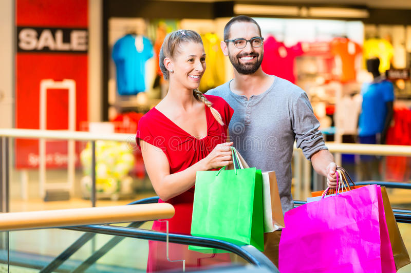 Couple in front of stores in mall shopping stock images