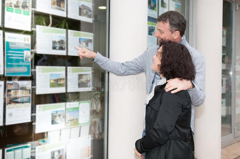 Couple in front of the window of a real estate agent. In street royalty free stock images