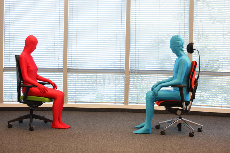 Couple in full body elastic suits sitting on armchairs in sunny space stock photo