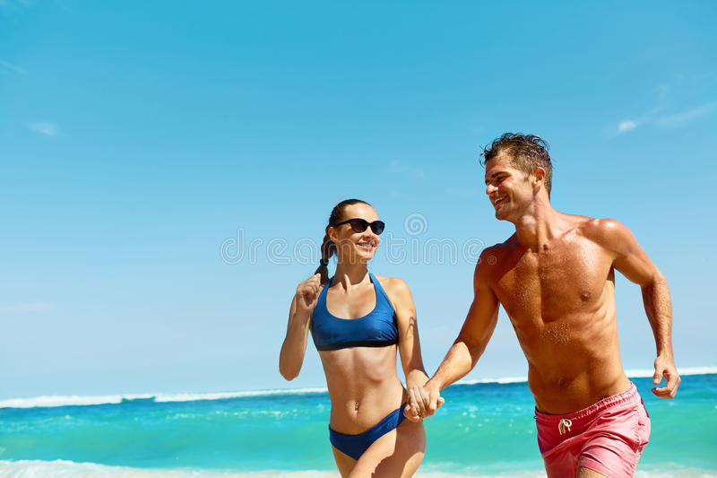 Couple Fun On Beach. Romantic People In Love Running At Sea royalty free stock image