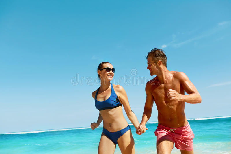 Couple Fun On Beach. Romantic People In Love Running At Sea stock images