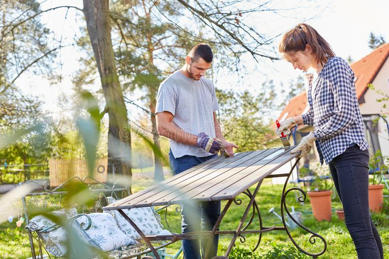 Couple in the furniture painting in the garden. Couple painting furniture and renovating in the garden stock image
