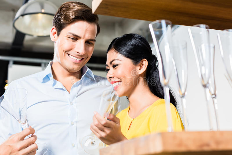 Couple in furniture store choosing glasses stock photo