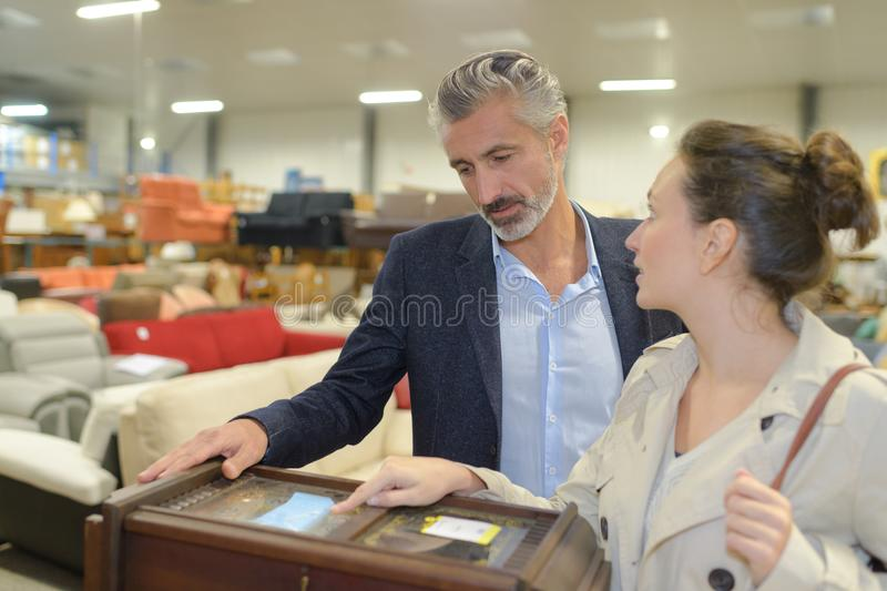 Couple in furniture store. Furniture royalty free stock images