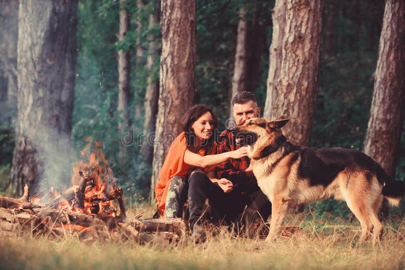 Couple with german shepherd dog near bonfire, nature background. Woman and handsome men on vacation, hiking, camping. Rest and relax concept. Couple in love or royalty free stock photography