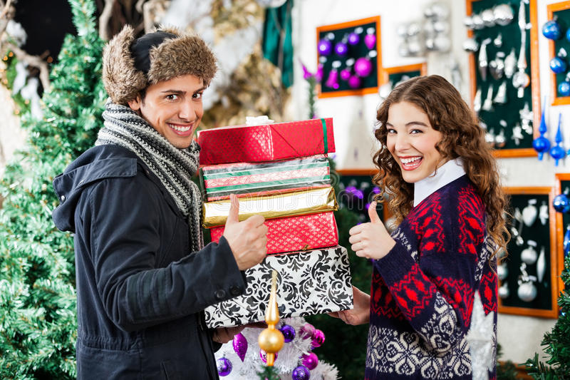Download Couple Gesturing Thumbs Up While Holding Christmas Stock Image - Image: 36934403