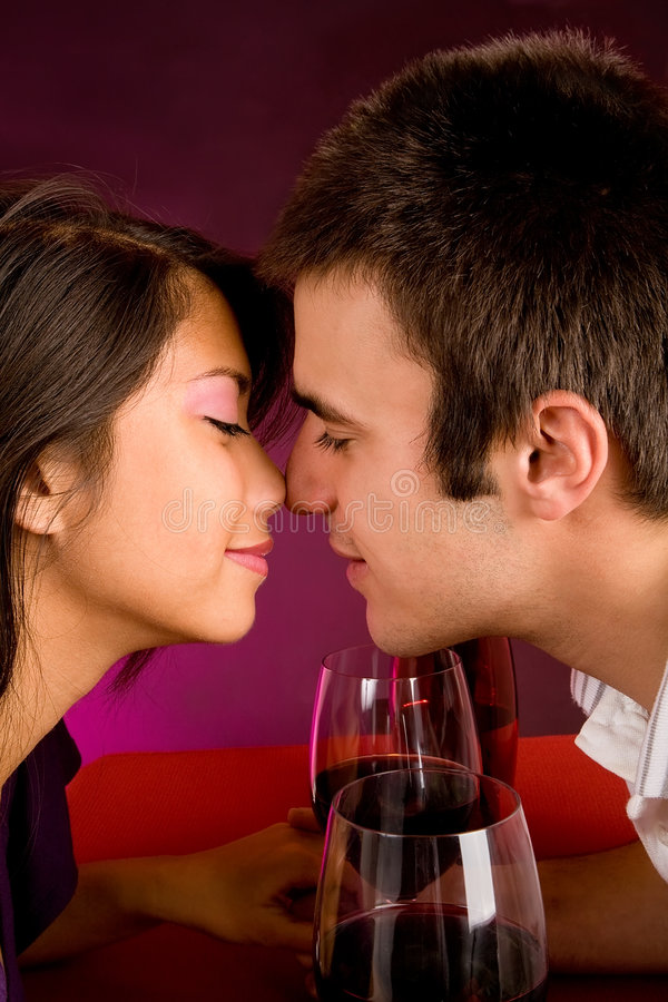 Couple Getting Closer While Having Wine. Couple sitting at a table drinking wine and getting close stock photo