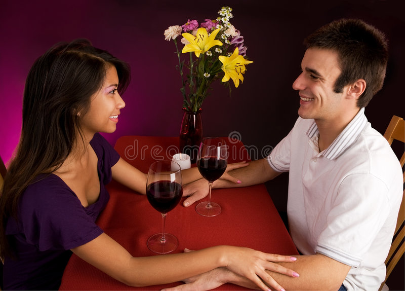 Couple Getting Closer While Having Wine. Couple sitting at a table drinking wine and getting close royalty free stock images