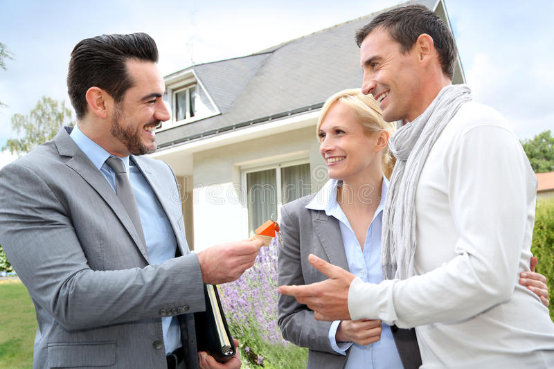 Couple getting keys of new home. Salesman giving home keys to property owners stock photos