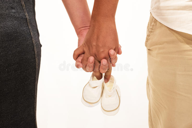 Couple getting ready for their first child. Couple gets ready for their first unborn child holding the baby shoes royalty free stock photos