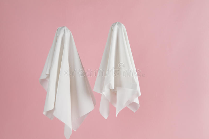Couple ghost back pink. Couple of white sheet ghost with doll`s eyes on a pink background. Minimal pop still life photography stock photography