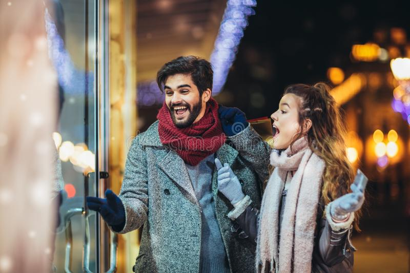 Couple with gift bag on Christmas lights background during walking in the city at evening royalty free stock photography