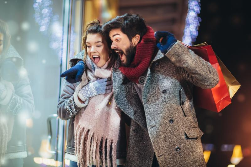 Couple with gift bag on Christmas lights background during walking in the city at evening royalty free stock photo