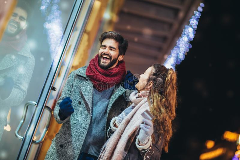 Couple with gift bag on Christmas lights background during walking in the city at evening royalty free stock images