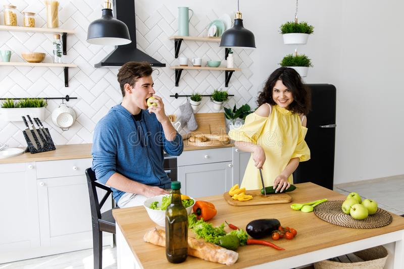 Young cute smiling couple cooking together at kitchen at home. A couple - a girl and a boy who spend time together for cooking. stock photo